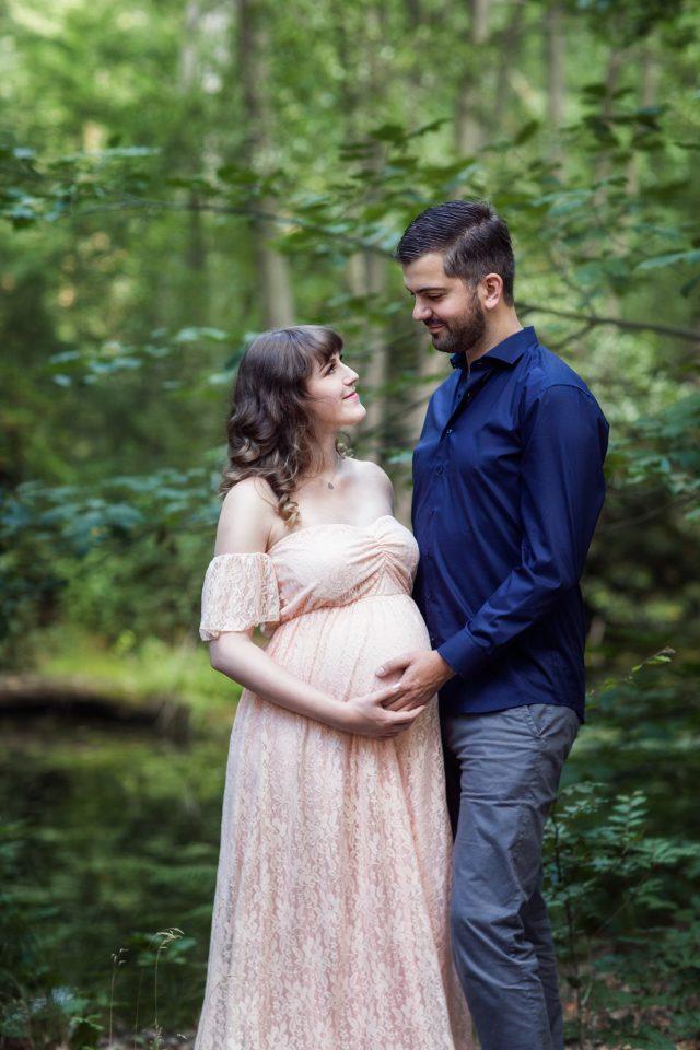 Verliebtes Pärchen im Wald. Schwangerschaftsshooting mit Partner. Romantische Pärchenbilder.