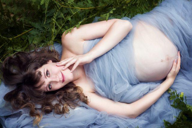Babybauchfotografie. Schwangere Frau, liegend im Wald. Tüllkleid. Schwangerschaftsbilder. Farn